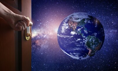 Wall mural hand opens empty room door to Planet earth from the space. Some