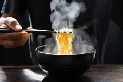 Wall mural Hand uses chopsticks to pickup tasty noodles with steam and smoke in bowl on wooden background, selective focus. Asian meal on a table, hot food and junk food concept