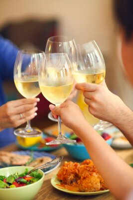 Hands of a group of people cheering with white wine