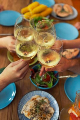 Hands of a group of people cheering with white wine and rising glasses on celebration at restaurant