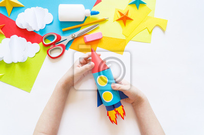 Wall mural hands of the child make a paper craft rocket. Cosmos clouds and stars colored paper. The creative process