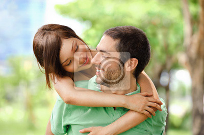 Happy girl embracing handsome male outside