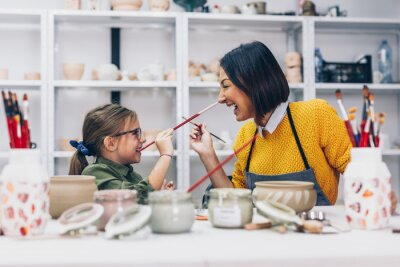 Wall mural Happy mother and daughter enjoying together in making clay pottery.