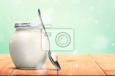 Healthy fresh  yogurt with spoon on background