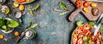 Wall mural Healthy vegetarian salad making preparation with tomatoes on rustic background, top view, banner, copy space