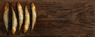 Wall mural herring sprats smoked wooden oak background