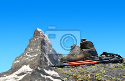 Hiking shoes and poles on the rock, in the background mount Matterhorn - Pennine Alps, Switzerland