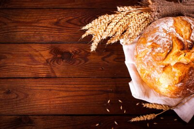 Wall mural Homemade bread on wooden background. Country style. Food baking background