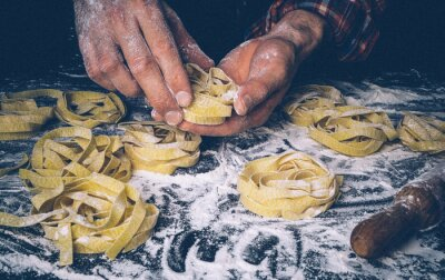 Wall mural Homemade uncooked pasta on black background. Making fresh italian fettuccine.