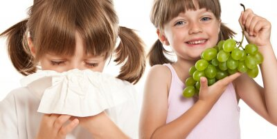 ill little girl with handkerchief and girl with fruit