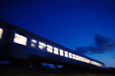 Wall mural Illuminated train traveling past at night