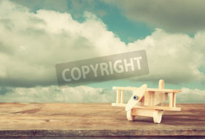 Wall mural image of wooden toy airplane over wooden table against cloudy sky. retro style image