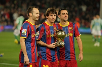 Wall mural Iniesta, Messi and Xavi of Barcelona with golden ball before a Spanish Cup match between FC Barcelona and Real Betis at the Nou Camp Stadium on January 12, 2011 in Barcelona, Spain