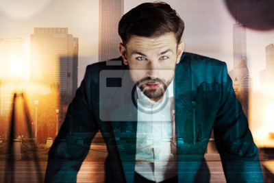 Wall mural Intense stare. Handsome bristled young man in a suit leaning on the table with both hands and staring at the camera intensely