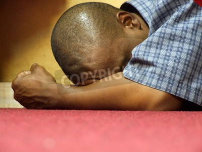 Wall mural Intensity - of Worship and Prayer. A black male in intense prayer, stress or contemplation at an all night prayer meeting in a christian church