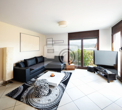 Wall mural Large living room with large black leather sofa, large screen and fantastic view