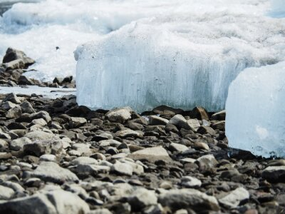Wall mural Large pieces of ice lie on a stone river coastline.