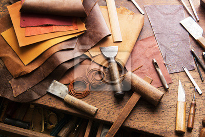 Wall mural Leather craft or leather working. Selected pieces of beautifully colored or tanned leather on leather craftman's work desk .