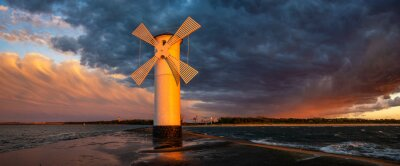 lighthouse in the shape of a windmill in Swinoujscie in Poland during the dramatic sunset
