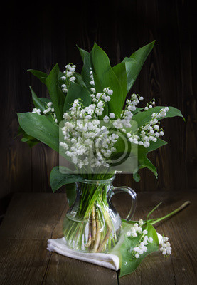 Lilies of the valley in a glass jug.