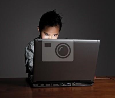 Little boy looking above laptop screen