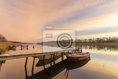 Łódka przy drewnianym pomoście nad jeziorem