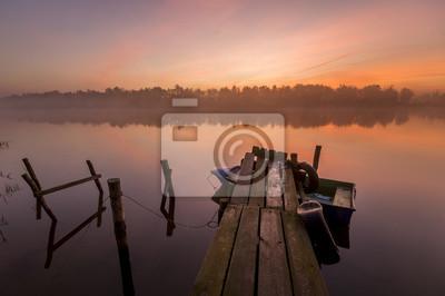 łódka zacumowana  do drewnianego pomostu