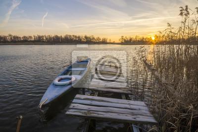 łódka zacumowana zimą do drewnianego pomostu