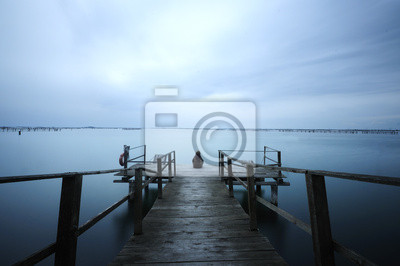 Lonely girl on a pier