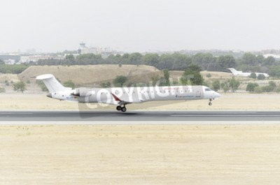 Wall mural MADRID, SPAIN - AUGUST 8th 2015: Aircraft -Bombardier Canadair CRJ-900-, of -Air Nostrum- airline, is landing on Madrid-Barajas -Adolfo Suarez- airport, on August 8th 2015.