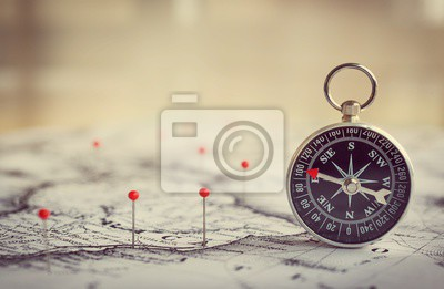 Magnetic compass on a world map conceptual of global travel , tourism and exploration. Macro photo.