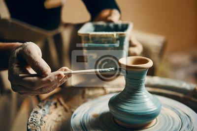 Wall mural Man painting handmade pottery at ceramic workshop