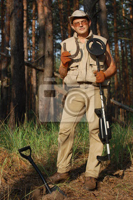 Man with metal detector and German WWII time horse-shoe