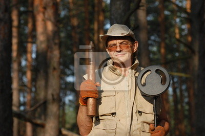 Man with metal detector and Soviet WWII 45-mm cannon-shell