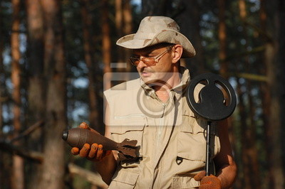 Man with metal detector and Soviet WWII 82-mm mortar-shell