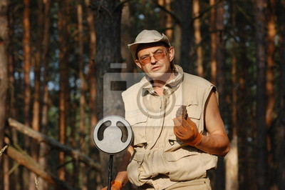 Man with metal detector and Soviet WWII F-1 hand-grenade