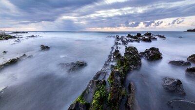 minimalistic sea landscape - rocks flooded due to waves, slow shutter speed