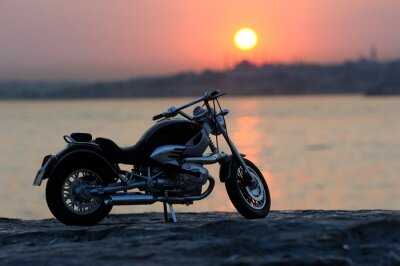 Wall mural Motorcycle on the rocks in sunset and golden hours