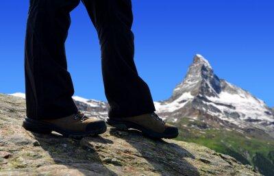 Mountain hiker on a trip in Pennine Alps, in the background Matterhorn peak, Switzerland.