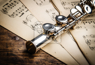 music background. Silver flute on an ancient musical background.