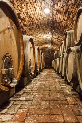 Wall mural Oak barrels in a underground wine cellar