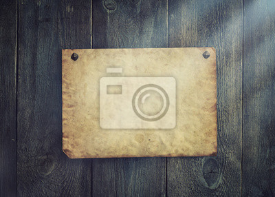 Old blank parchment on aged wood background and light rays.