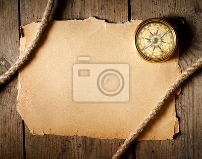 Old compass and rope on old paper.