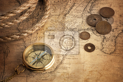 old compass, old coins and rope on vintage map