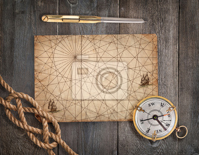 Old compass, rope, divider and vintage map on the wood desk.