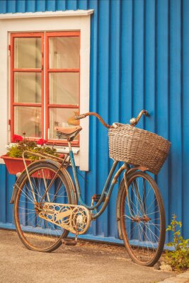 Wall mural Old rusty lady bicycle in front of a Swedish house