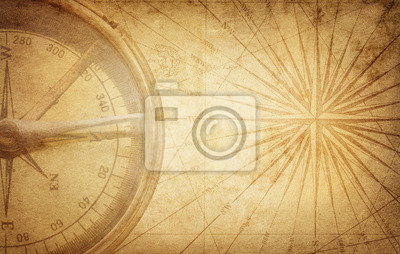Old vintage retro compass on ancient map. Survival, exploration and nautical theme grunge background