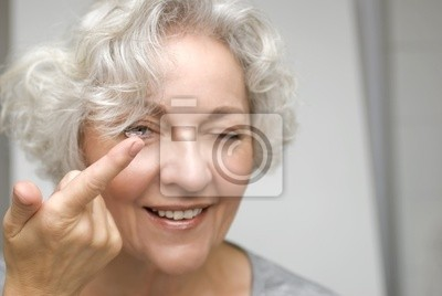 older woman examining a contact lens in more detail