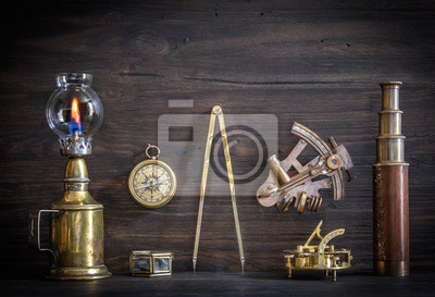 Overhead view of pirate or sailor gear laid out for a backpacking trip on a old wood floor. Items include, rope, compass, money, binoculars, sextant , shell. Stories background.