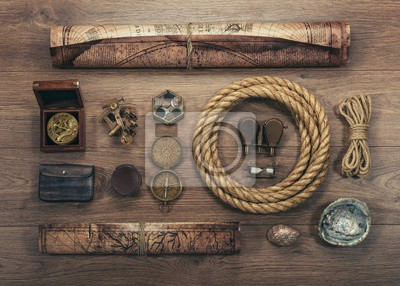Overhead view of pirate or sailor gear laid out for a backpacking trip on a old wood floor. Items include, rope, compass, money, map, binoculars, hourglass, sextant , shell. Stories background.